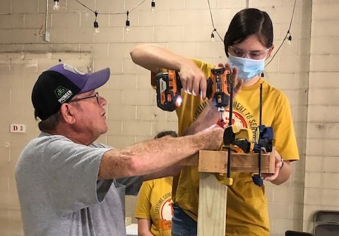Volunteer partners with an adult leader to learn how to properly use power tools.